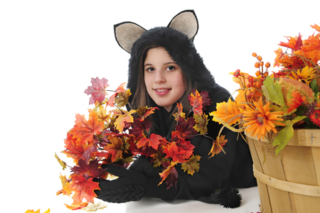basketful: A pretty young teen happily laying on her belly with a paw-full of colorful leaves.  Shes laying behing a basket of more fall foliage.  On a white background.