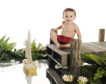 wooden dock: An adorable preschool swimmer sailing his toy boat from an old wooden dock.  Surrounded by foiliage.  On a white background. Stock Photo