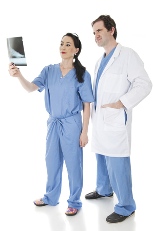 medical personnel: Two medical personnel looking pleased as they check a patients food X-ray together. Isolated on white. Stock Photo