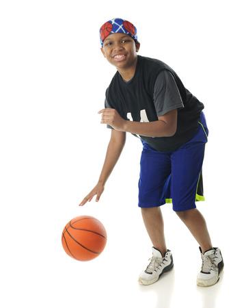 ビューアーを見て彼は喜んで彼のバスケット ボールをドリブル、プレティーンの少年。 白地。