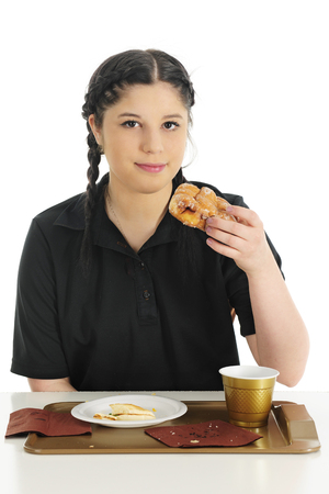 fritter: A pretty teen girl looking at the viewer as shes ready to enjoy a glazed fritter, the last of her fast food breakfast.  On a white background.