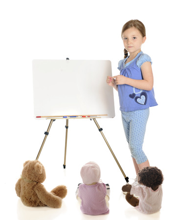 A young elementary girl standing beside her whiteboard ready to begin class for the toy students.  On a white background. photo