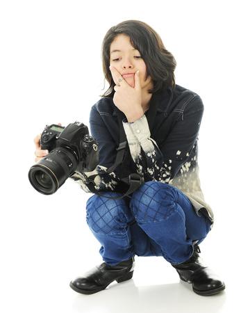 en cuclillas: Un fotógrafo en cuclillas joven que estudia cuidadosamente la imagen en la parte posterior de su cámara. Sobre un fondo blanco. Foto de archivo
