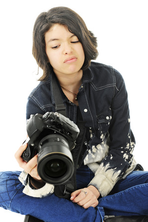 yuck: A corner image of an attractive young teen unhappy with the image in the back of her pro camera.  On a white background.
