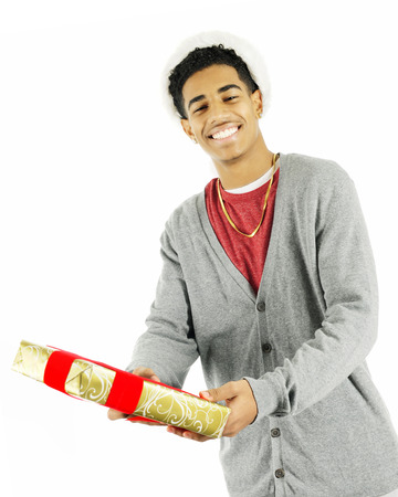 A tall teen man happily handing a wrapped Chritmas gift to the viewer.  On a white background.