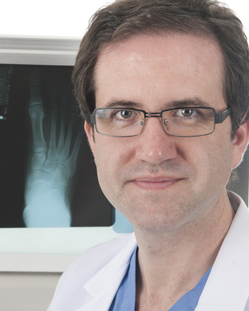 adult bones: Close-up image of a doctor before his X-ray lightbox with the image of a human foot. Stock Photo