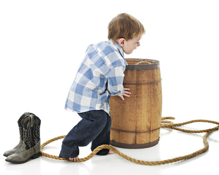 barefoot cowboy: An adorable 2-year-old cowboy pushing a rustic old barrel thats surrounded by a thick rope.  On a white background.