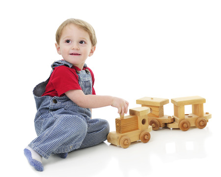 An adorable toddler in pin striped overalls as he pulls the engine of a wooden toy train.  On a white background.