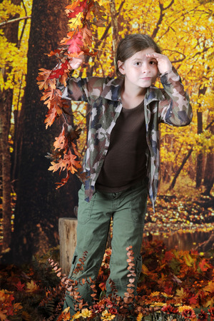 shielding: A pretty elementary girl in an autumn woods shielding her eyes as she peers into the distance. Stock Photo
