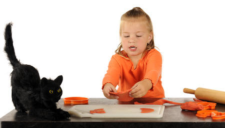 cookie cutter: A cute preschooler picking up the pumpkin shape shes just created with a cookie cutter.  A scary black cat sits nearby. Stock Photo