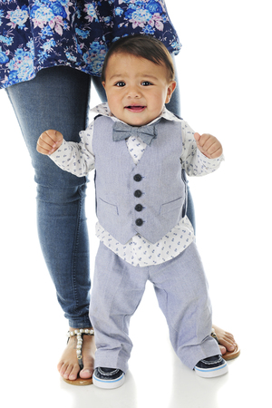 without legs: An adorable, dressed-up baby boy looking mighty worried as he stands without hanging on.  His mothers legs and feet are sirectly behind him giving him some support.  On a white background.