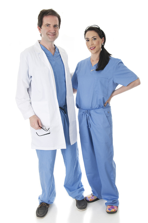 looking at viewer: Full length image of a man and woman health care worker looking at the viewer with their arms around each other.  On a white background.