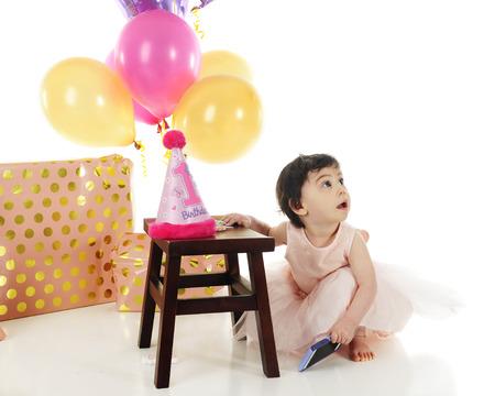 en cuclillas: Una niña adorable en su primer cumpleaños. Ella está en cuclillas en su vestido rosa mirando hacia arriba lejos de sus regalos y globos. Sobre un fondo blanco.