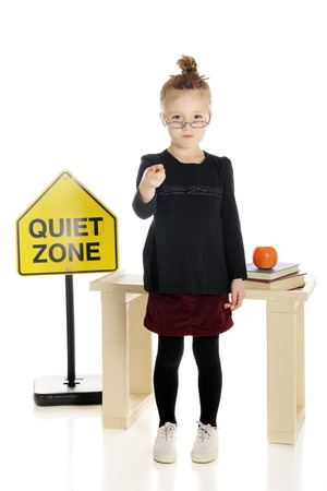 scowling: An adorable little teacher scowling at and pointing to the viewer in front of her desk and a Quiet Zone sign.  On a white background.