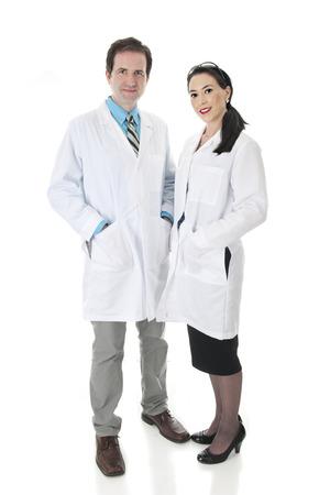 Una imagen de cuerpo entero de un hombre y trabajadores de la salud femenina. Ellos están de pie juntos y felices en sus batas de laboratorio. Sobre un fondo blanco.
