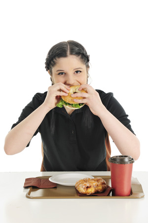 fritter: A attractive een girl happily biting into a breakfast bagle sandwich with a fritter and mug of coffee on the table before her.  On a white backtround. Stock Photo