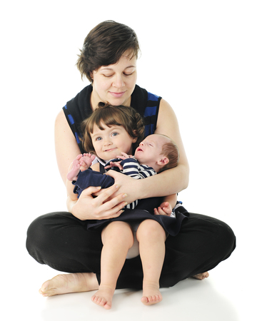 A barefoot mother sitting on the floor with her toddler daughter and newborn son in her arms.  On a white background.