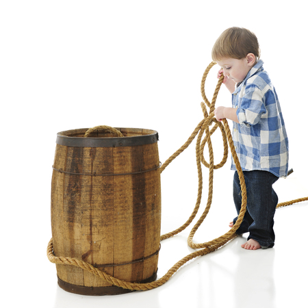 barefoot cowboy: An adorable 2-year-old cowboy pulling rope around a rustic old barrel.  On a white background. Stock Photo