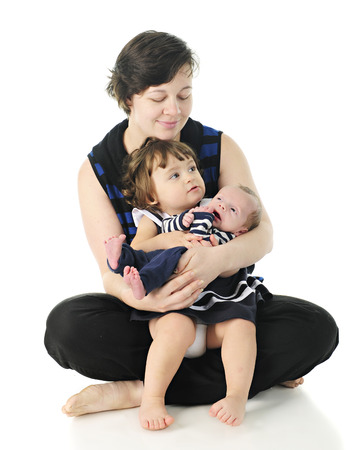 A young, barefoot mom sitting on the floor holding and smiling down on her toddler daughter and newborn son.  On a white background.