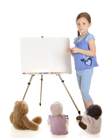 A young elementary girl standing beside her whiteboard ready to begin class for the toy students.  On a white background.