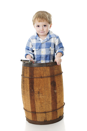 An adorable preschool cowboy standing in a rustic old barrel.  On a white background.