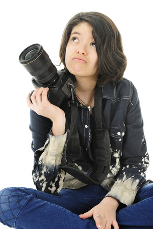 looking in corner: Corner image of a young teen photographer looking up wonderingly as she supports her pro camera on her shoulder.  On a white background.