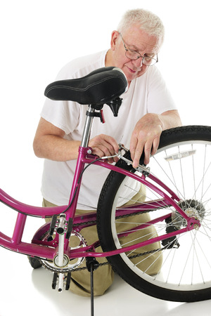 man kneeling: A senior man kneeling as he fixes his granddaughters bikes brakes.  On a white background.