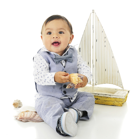 An adorable, dressed up baby boy looking up happily as he hold two beautiful sea shells.  On a white background. Reklamní fotografie