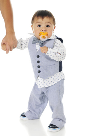 An adorable dressed-up baby boy, standy with his mother firmly holding his hand and a binky plugged in his mouth.  On a white background.