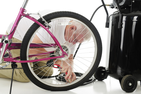 man kneeling: A senior man kneeling beside a girls bike and an aircompressor as he fills his granddaughters bike tire with air. On a white background.