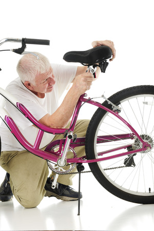 crescent wrench: A senior man adjusting his grranddaughters bicycle seat.  On a white background.