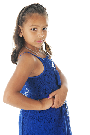 royal blue: A beautiful elementary Hispanic girl looking back at the viewer in her lacy royal blue summer dress.  On a white background.