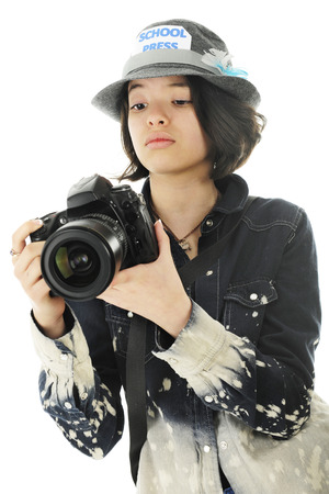 A pretty young teen checking camera settings while getting  photographs for her school yearbook.  On a white background.