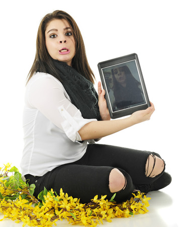 A pretty young teen sitting among forsythia, making an ungly face while holding the selfie on her ipad for the viewer to see.  On a white background.