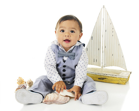 dressed up: An adorable, dressed up baby boy playing with sea shells in front of his toy sailboat.  On a white background.