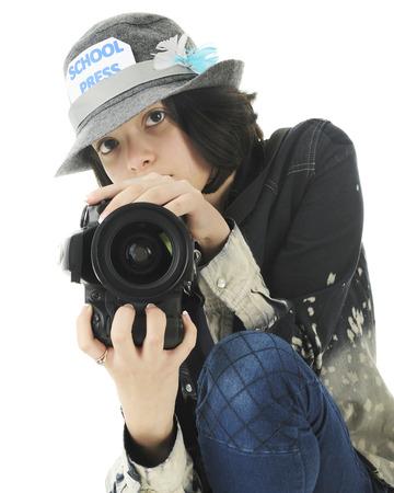 cuclillas: Una atractiva joven escolar adolescente fot�grafo cuclillas para disparar desde una posici�n baja. Sobre un fondo blanco.
