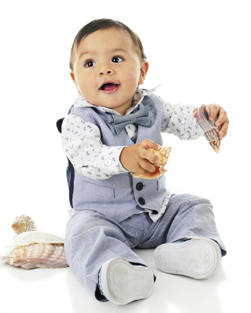 dressed up: An adorable, dressed up baby boy happily playing with a variety of sea shells.  On a white background.