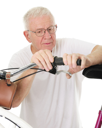 hand brake: Closeup of a senior man working on his granddaughters bikes hand brake.  On a white background.