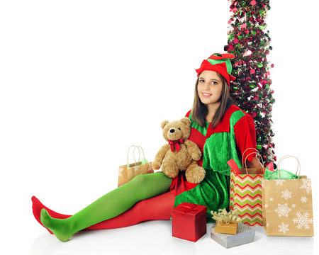 panty hose: A pretty teen elf relaxed by a sparkly tree and surrounded by Christmas gifts.  On a white background.