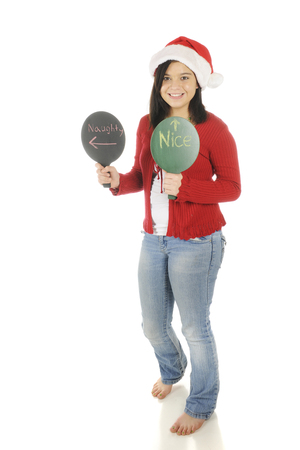 A pretty teenage girl in a Santa hat.  Shed holding signs indicating shes nice, while her companion (not included) is naughty.  On a white background.