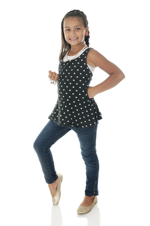 sassy: A pretty elementary girl standing and sassy in her polka dot top and jeans.  On a white background. Stock Photo