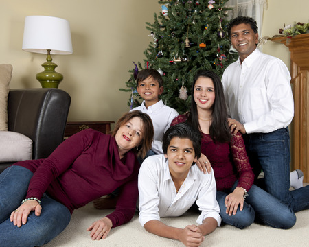 Portrait of a biracial family of five posing before thier Christmas tree. photo