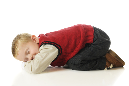 bottoms: An adorable preschooler in slacks and a sweater vest, bottoms up feigning sleep.  On a white background.