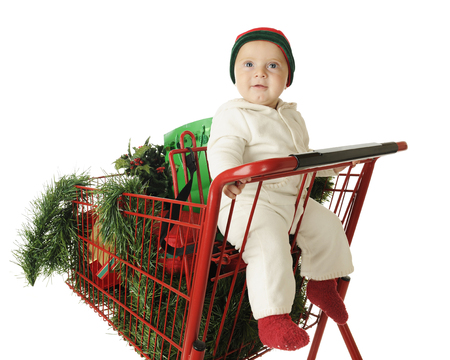 An adorable baby boy happily riding in the child's seat of a red shopping cart filled with Christmas goodies.  On a white background. photo