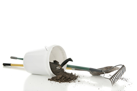shovel in dirt: A white bucket of spilled dirt with a hand spade.  A dirty garden rake and shovel nearby.  On a white background with  space above for your text.