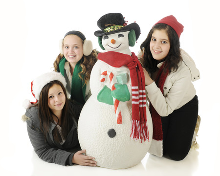 Three young teens happily posing with a Christmas snowman.  On a white background,. photo