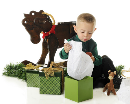 An adorable preschooler opening his gifts on Christmas Day.  On a white background. photo