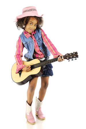 black cowgirl: A full-length image of a young cowgirl happily strumming a classical guitar.  On a white background. Stock Photo