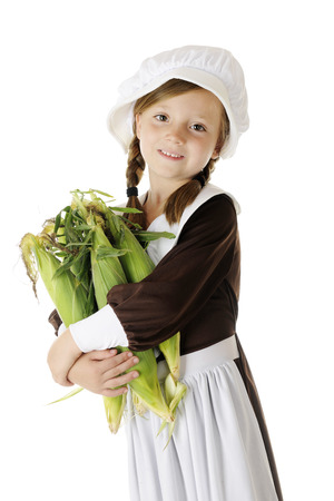 An attractive young Pilgrim girl with an armload of fresh corn in the husks.  On a white background. photo