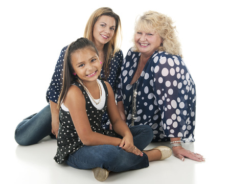 Three generations of women -- an elementary girl with her mother and grandmother.  All wear navy blue and white poka dotted outfits.  On a white background.